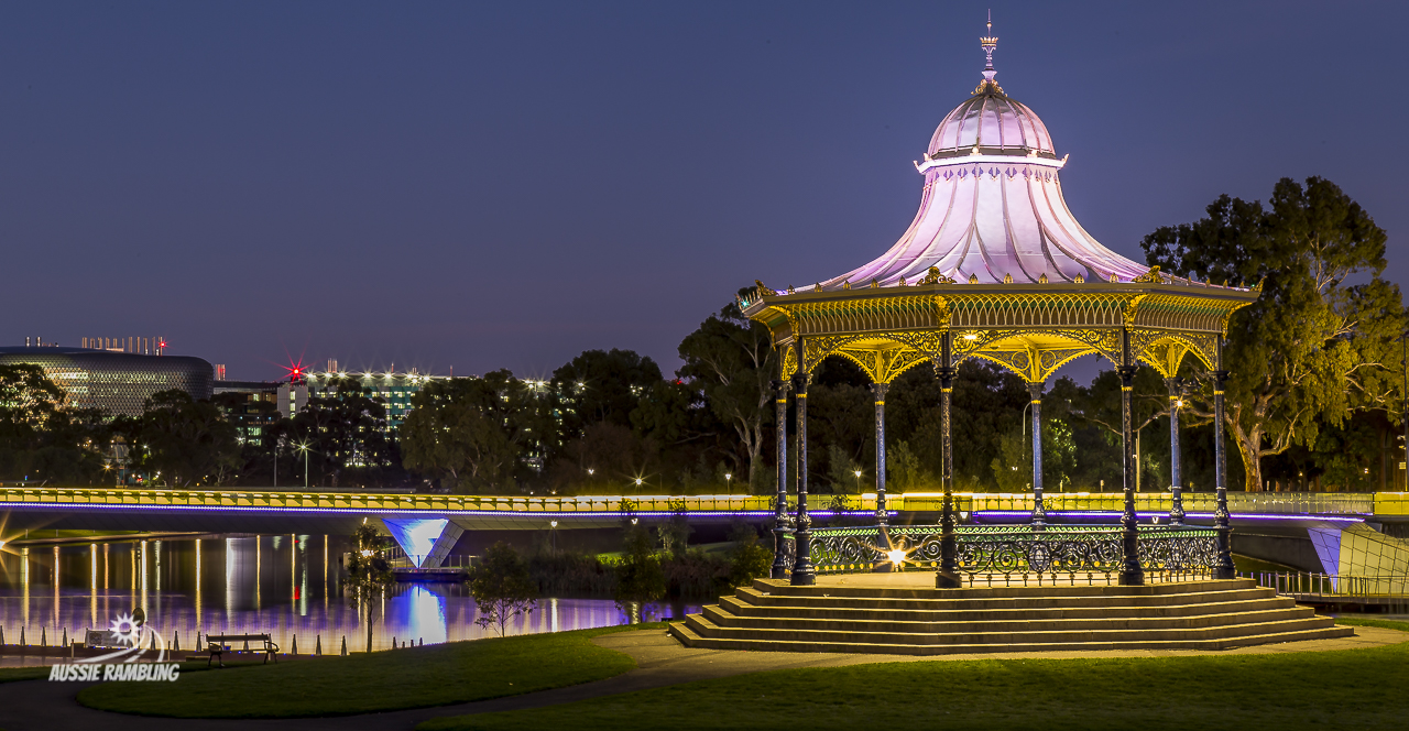 Elder Park Rotunda situated on the banks of the Torrens River, with the walking bridge all lit up.