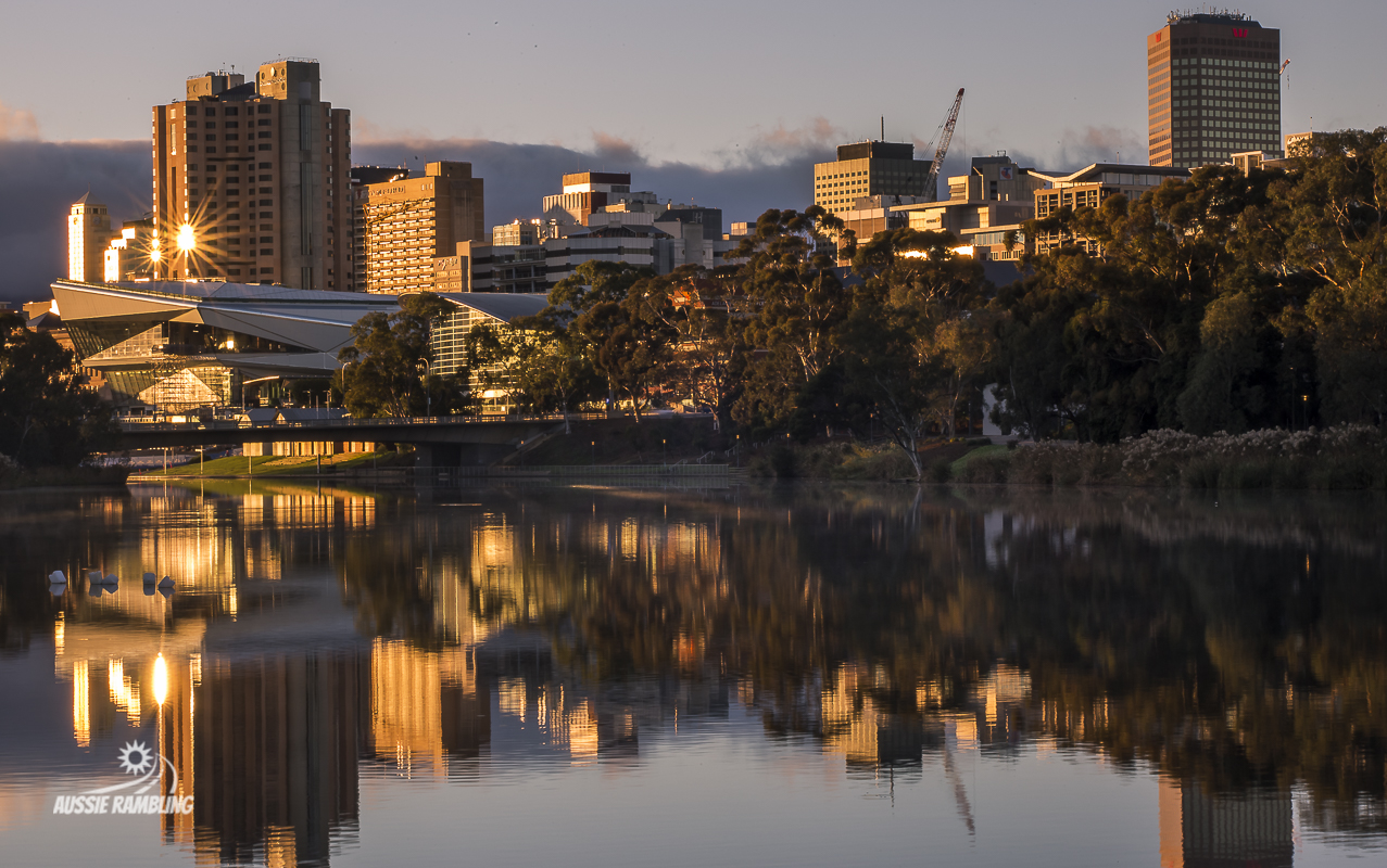 A shelf cloud sitting behind Adelaide City as the sunrises over the Torrens River.